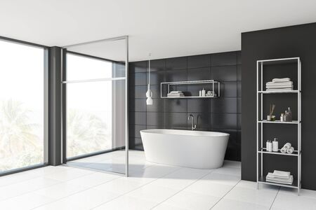 Corner of stylish bathroom with gray tile and glass walls, white floor, comfortable bathtub and shelves with towels and beauty products. 3d rendering Фото со стока
