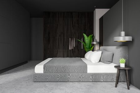 Side view of minimalistic master bedroom with gray and dark wooden walls, concrete floor, comfortable king size bed with bedside table and potted plant. 3d rendering
