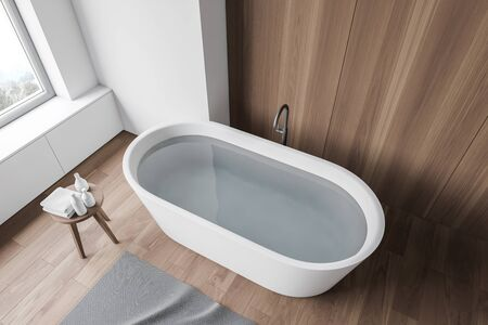 Top view of white bathtub with water standing in modern bathroom with white and wooden walls, wooden floor and gray carpet. 3d rendering Stok Fotoğraf