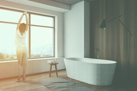 Woman in pajamas standing in luxury bathroom with white and wooden walls, comfortable bathtub and window with mountain view. Toned image double exposure Stok Fotoğraf