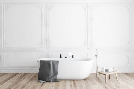 Interior of classic style bathroom with white walls, wooden floor, comfortable bathtub with gray towel on it and small chair with beauty products. 3d rendering