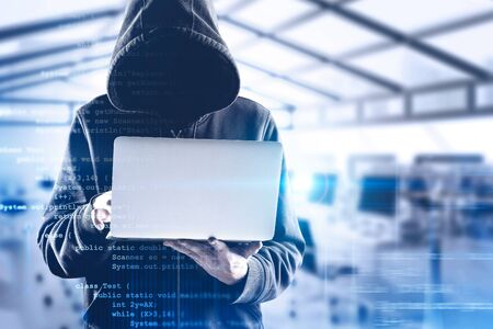 Young unrecognizable hacker in black hoodie using laptop over blurry office background with double exposure of lines of code. Concept of identity theft and cyber security. Toned image Stockfoto