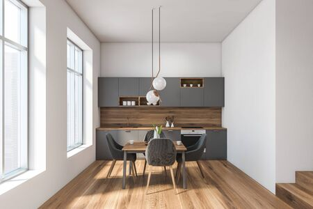 Interior of luxury kitchen with white and wooden walls, wooden floor, grey countertops and cupboards and square wooden dining table with gray chairs. 3d rendering