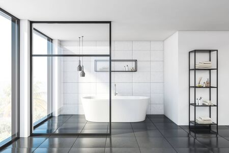 Interior of stylish bathroom with white tile and glass walls, gray floor, comfortable bathtub and shelves with towels and beauty products. 3d rendering Stockfoto