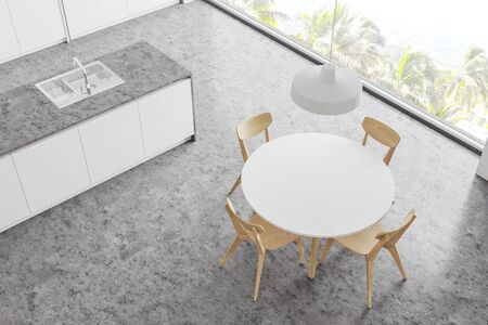 Top view of stylish panoramic kitchen with white walls, concrete floor, white countertops and round dining table with wooden chairs. 3d rendering