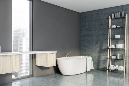 Modern bathroom with gray and tiled walls, tiled floor, comfortable bathtub standing in the corner and wooden cabinets near narrow window. Shelves with towels and beauty products. 3d rendering Stockfoto