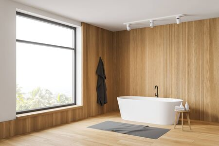 Corner of minimalistic bathroom with wooden and white walls, wooden floor and comfortable white bathtub. Towel hanging on the wall. 3d rendering Stockfoto