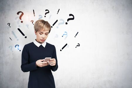 Serious young woman looking at her smartphone standing near concrete wall with question and exclamation marks drawn on it. Concept of looking for answer and online search. Mock up Banco de Imagens
