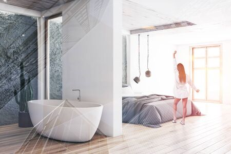 Rear view of young woman in nightgown standing in modern bedroom with white walls,wooden floor and comfortable bathroom with bathtub next to it. Toned image double exposure 스톡 콘텐츠