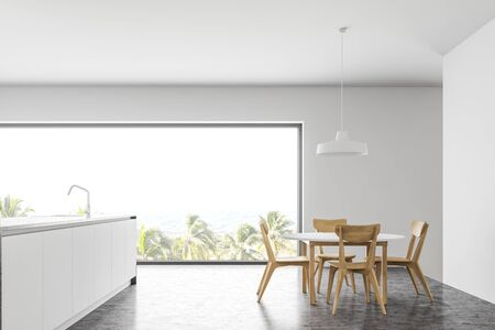 Interior of minimalistic panoramic kitchen with white walls, concrete floor, panoramic window, white island with built in sink and round dining table with wooden chairs. 3d rendering