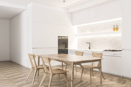 Corner of stylish kitchen with white walls, wooden floor, white countertops with sink and stove, two built in ovens and wooden dining table with chairs. 3d rendering