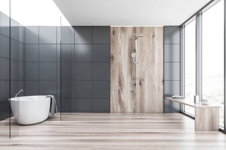 Interior of comfortable bathroom with grey tile and glass walls, wooden floor, comfortable bathtub with towel hanging on it and vertical shower with wooden bench. 3d rendering Stockfoto