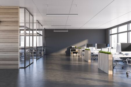 Interior of modern office with grey walls, dark concrete floor, rows of computer tables with flower beds and panoramic windows. 3d rendering 写真素材