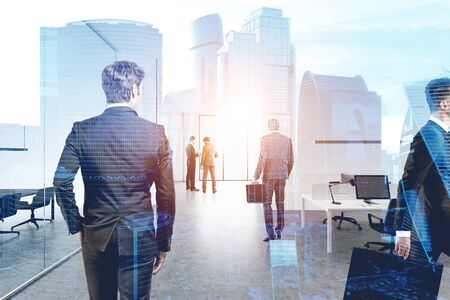 Diverse business people working together in modern office with double exposure of Moscow city panorama. Concept of business lifestyle and teamwork. Toned image