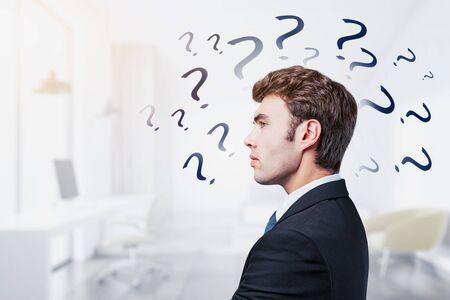 Vista lateral del joven empresario de pie en la oficina borrosa con signos de interrogación dibujados sobre él. Concepto de buscar respuesta. Exposición doble