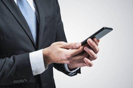 Close up of unrecognizable businessman in dark suit and gray tie using smartphone over gray background. Concept of communication and internet Stock Photo