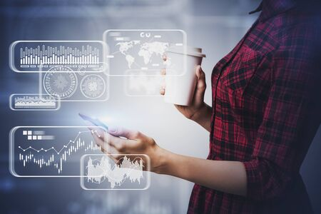 Unrecognizable businesswoman in casual clothes with smartphone and coffee standing over gray background with double exposure of blurry HUD infographic interface. Concept of big data. Toned image