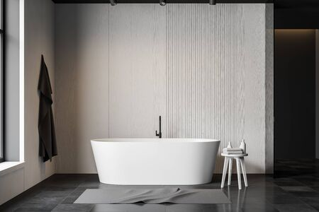 Interior of minimalistic bathroom with white and grey walls, gray tiled floor and comfortable white bathtub. Towel hanging on the wall. 3d rendering Stockfoto
