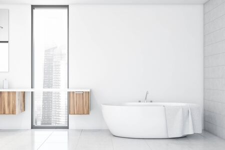 Interior of modern bathroom with white and tiled walls, tiled floor, comfortable bathtub standing in the corner and wooden cabinets near narrow window. 3d rendering