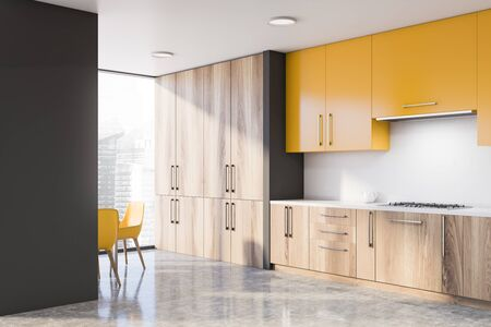 Corner of stylish kitchen with gray and white walls, concrete floor, wooden countertops with sink and stove and yellow cupboards. Chairs near panoramic window. 3d rendering