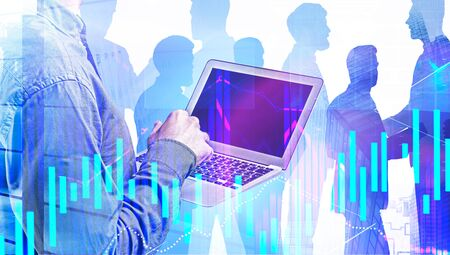 Unrecognizable businessman with laptop working in blurry city with business people in background and double exposure of digital charts. Concept of trading and teamwork. Toned image Imagens