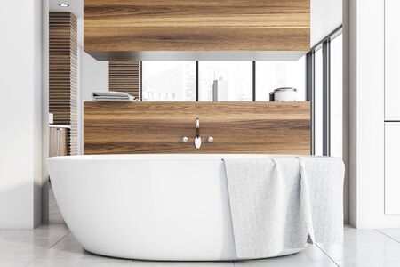 Interior of modern bathroom with white and wooden walls, tiled floor, comfortable bathtub with mirror above it and wooden shelves with towels and beauty products. 3d rendering