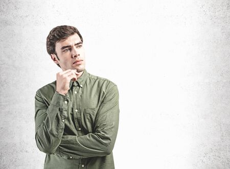 Portrait of pensive young businessman in green shirt with brown hair standing near concrete wall. Concept of business planning. Mock up
