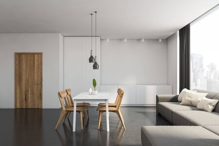 Interior of comfortable modern dining room with white walls, concrete floor, comfortable gray sofa with cushions and white table with wooden chairs. 3d rendering