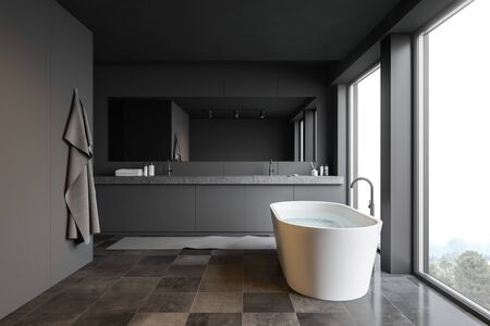 Interior of modern bathroom with gray panel walls, tiled floor, panoramic windows, comfortable bathtub and double sink with horizontal mirror. 3d rendering