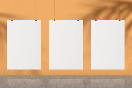 Three blank white mock up posters hanging near orange wall with palm tree shadows. Concept of advertising and art. 3d rendering
