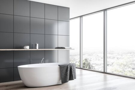 Corner of modern bathroom with grey tile walls, wooden floor, panoramic window with beautiful view and comfortable bathtub with shelf above it. 3d rendering