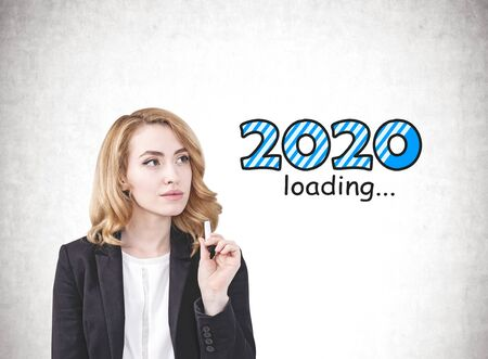 Thoughtful beautiful ginger businesswoman standing near concrete wall with 2020 loading written on it. Concept of planning and new year expectation Stock Photo