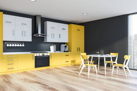 Interior of modern kitchen with dark gray walls, wooden floor, yellow countertops, white cupboards and round dining table with chairs. 3d rendering
