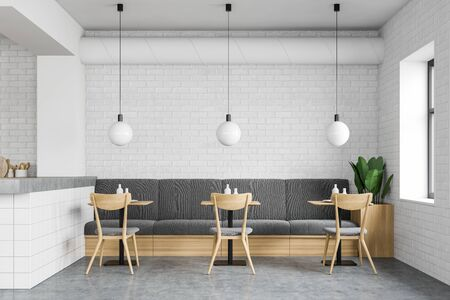 Interior of modern loft restaurant with white brick walls, concrete floor, comfortable grey sofa with square wooden tables and chairs. 3d rendering
