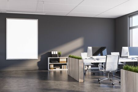 Interior of modern office with grey walls, dark concrete floor, rows of computer tables with flower beds and vertical mock up poster frame. 3d rendering 写真素材