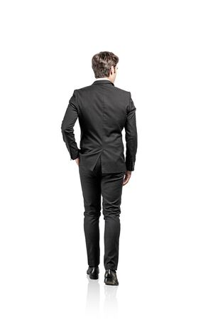 Rear view of young businessman with short brown hair wearing dark suit walking and looking sideways. Isolated full length portrait.