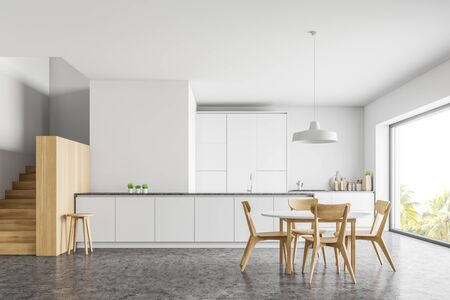 Interior of modern kitchen with white walls, concrete floor, wooden stairs, white countertop and bar and round dining table with chairs. 3d rendering