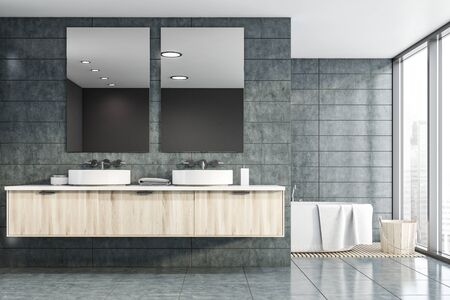 Interior of stylish bathroom with gray tile walls and floor, double sink standing on wooden countertop with two mirrors and bathtub with bucket near it. Concept of spa. 3d rendering