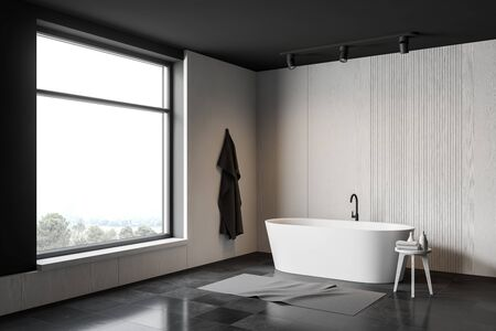 Corner of minimalistic bathroom with white and grey walls, gray tiled floor and comfortable white bathtub. Towel hanging on the wall. 3d rendering
