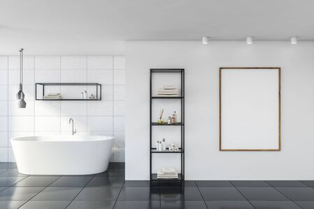 Interior of stylish bathroom with white tile walls, gray floor, comfortable bathtub, vertical mock up poster and shelves with beauty products. 3d rendering Stockfoto