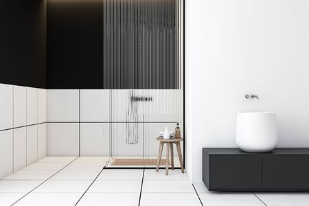 Interior of modern bathroom with white and black walls, tiled floor, shower stall with glass wall and massive sink standing on gray countertop. 3d rendering 写真素材