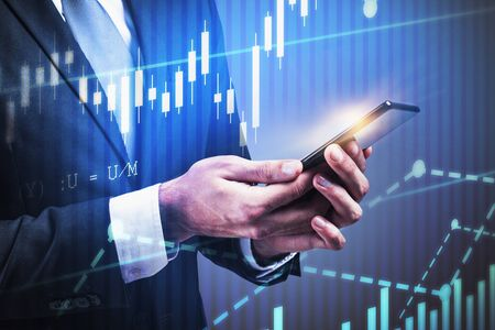 Empresario irreconocible mirando smartphone sobre fondo gris con doble exposición de gráficos digitales. Concepto de estilo de vida comercial y empresarial. Imagen tonificada