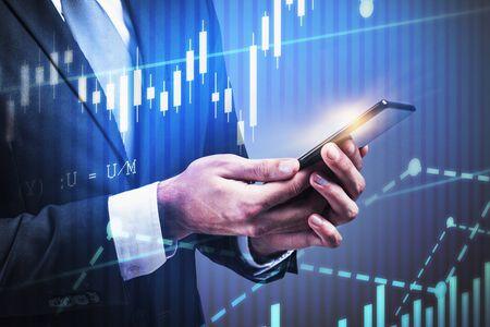 Nicht erkennbarer Geschäftsmann, der Smartphone über grauem Hintergrund mit Doppelbelichtung digitaler Diagramme betrachtet. Konzept des Handels und des Geschäftslebensstils. Getöntes Bild