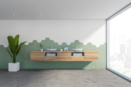 Interior of stylish panoramic bathroom with white and green hexagon tile walls, concrete floor, panoramic window and comfortable double sink standing on wooden countertop. 3d rendering