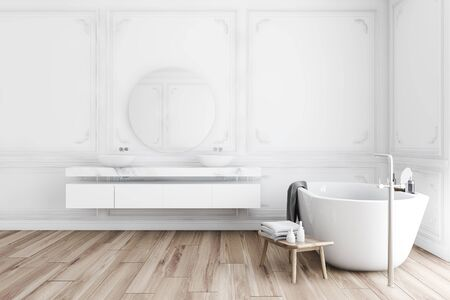 Interior of classic style bathroom with white walls, wooden floor, comfortable bathtub with gray towel on it and double sink with round mirror. 3d rendering