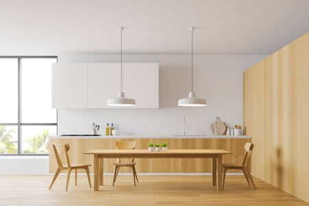 Cozy wooden dining table with chairs standing in modern kitchen interior with white and wooden walls, white cupboards and wooden countertops. 3d rendering Stock Photo