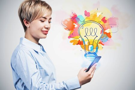 Smiling blonde businesswoman looking at her smartphone standing near concrete wall with colorful lightbulb drawn on it. Concept of bright idea Stok Fotoğraf