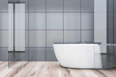 Interior of comfortable bathroom with grey tile and glass walls, wooden floor and comfortable bathtub with towel hanging on it. 3d rendering Stockfoto