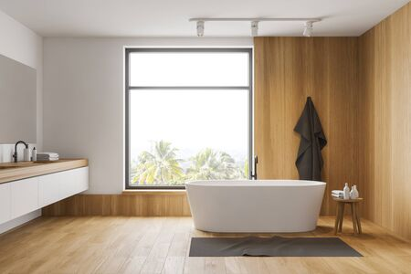Interior of modern bathroom with white and wooden walls, wooden floor, comfortable white bathtub and sink standing on white countertop. Window with tropical view. 3d rendering Stockfoto