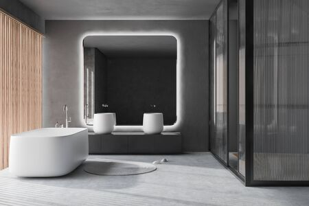 Interior of luxury bathroom with concrete walls and floor, white bathtub, massive double sink standing on gray countertop with big square mirror and glass wall shower stall. 3d rendering